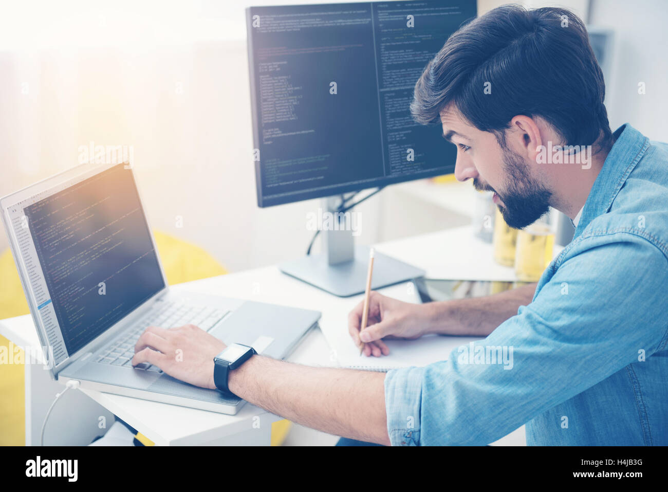 Concentrated man coding on a laptop - Stock Image