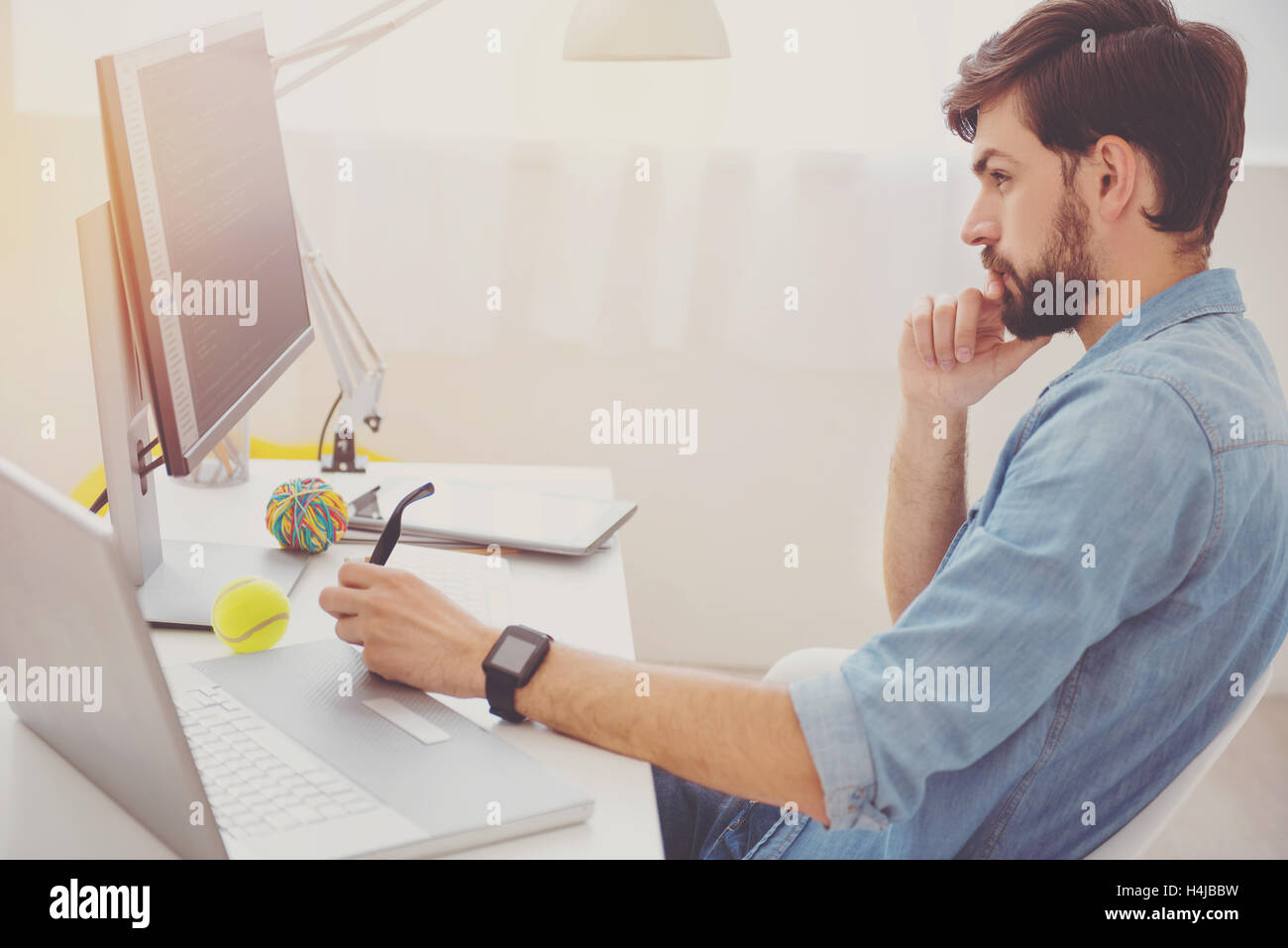 Handsome programmer analyzing his work - Stock Image