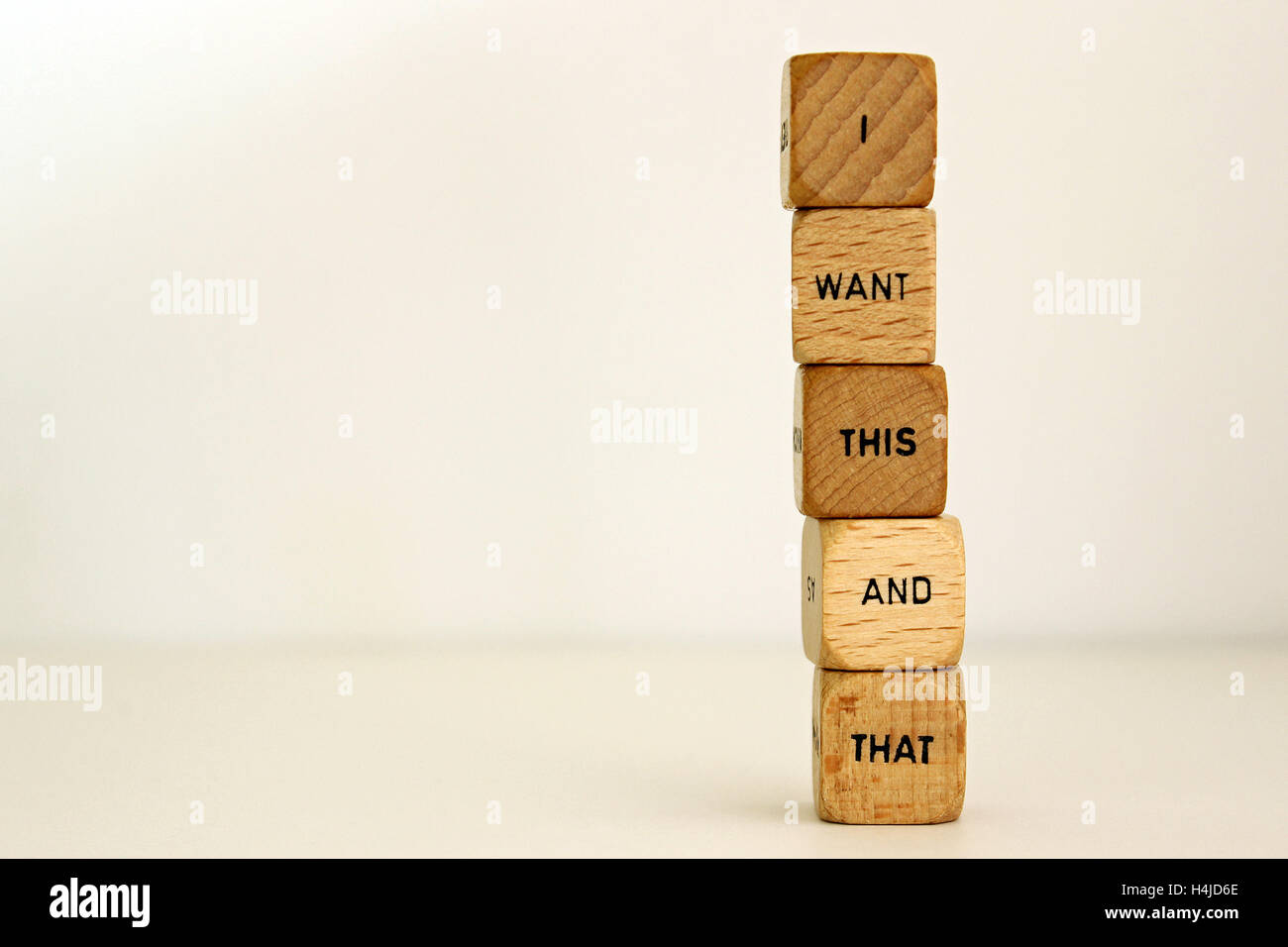 :I want this and that' printed on wood dice against white background. - Stock Image