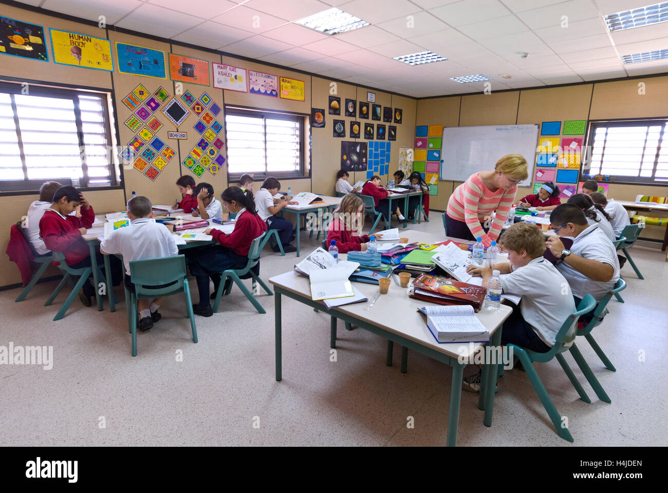 Junior school children with female teacher concentrate on their studies at their desks in modern airy light school - Stock Image