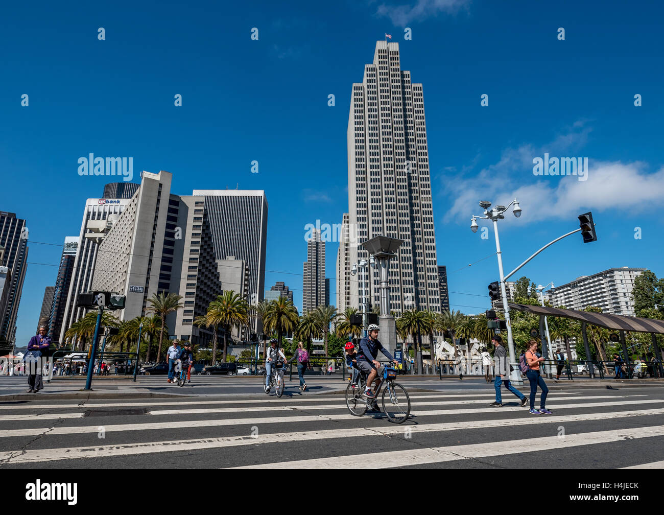 San Francisco's Embarcadero street scene at crosswalk, pedestrians and bicyclists downtown financial district - Stock Image