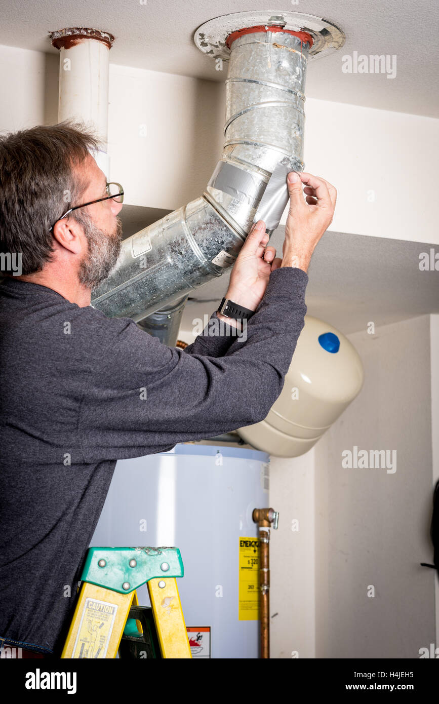 Adding tape to home duct work standing on a ladder - Stock Image
