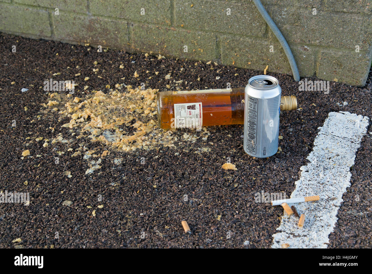 Pile of vomit on car park floor with can, bottle and cigarette butts - Stock Image