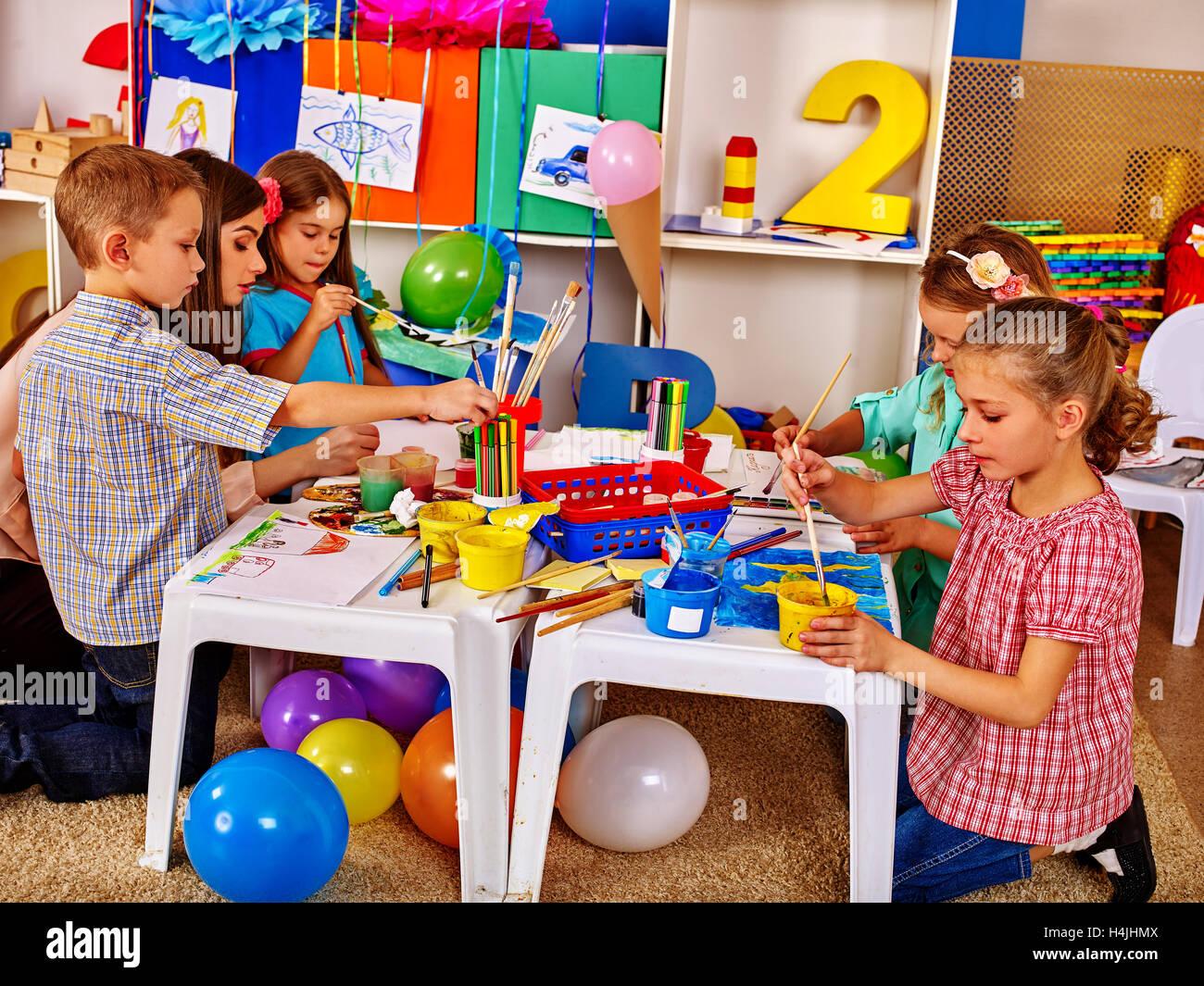 Woman Teaches Children To Handicrafts Made Of Paper In Kindergarten