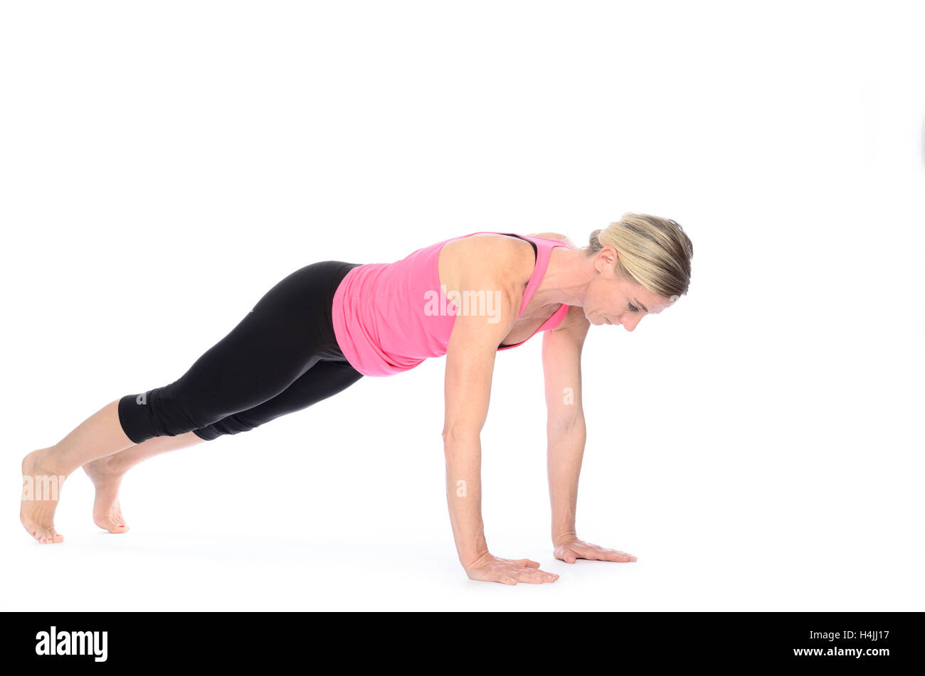 Healthy fit woman working out doing press-ups and balancing on her hands and toes isolated on white with copy space - Stock Image