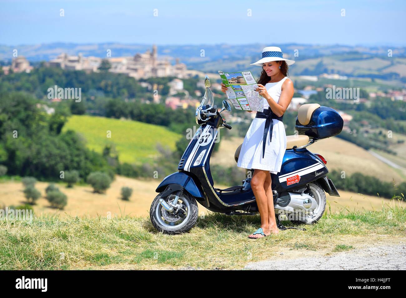 Fashionable Woman Looking At Map With Vespa Primavera