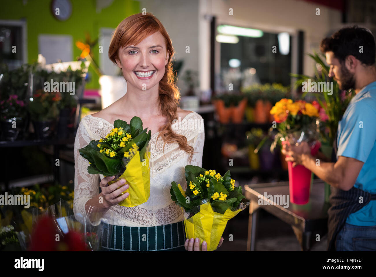 Woman holding flower bouquet while man working in the background Stock Photo