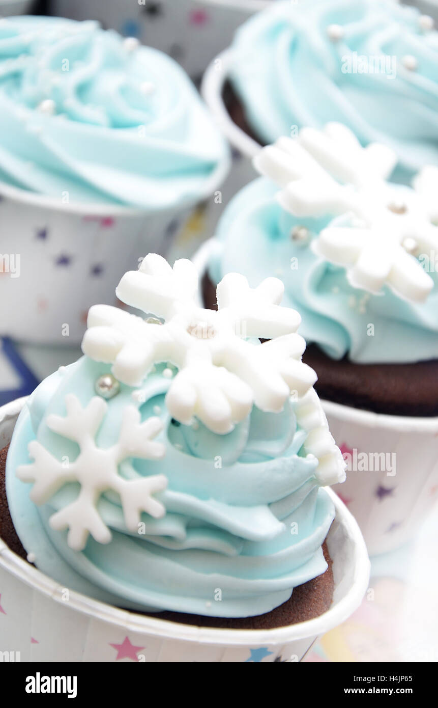 cup cakes with snowflakes decorating in the color of light blue for a celebrating birthday party - Stock Image