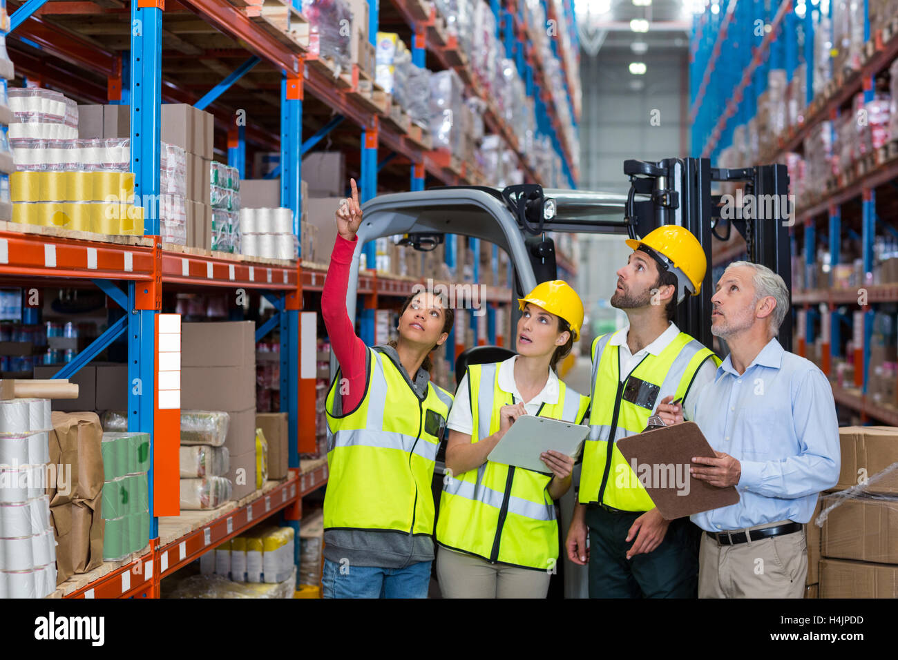 Warehouse manager and co-workers discussing over clipboard - Stock Image