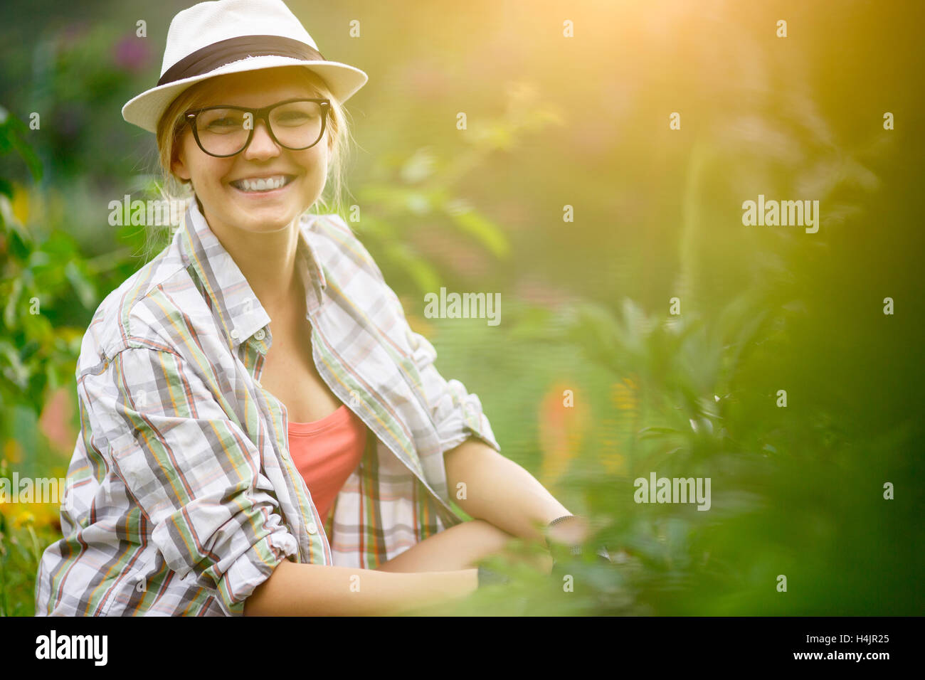Happy girl farmer takes care of plants in her garden - Stock Image