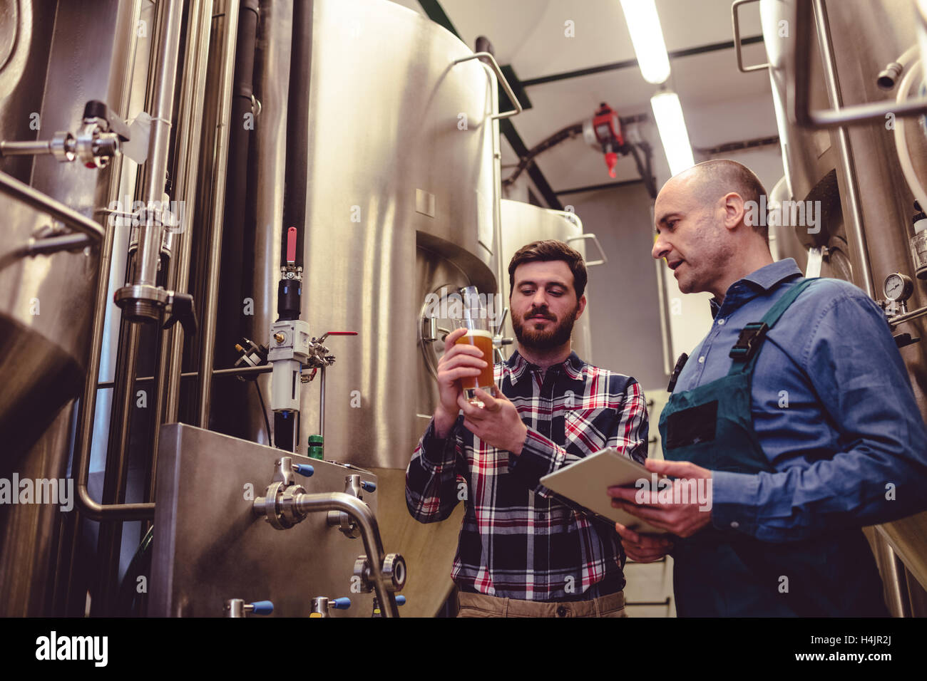 Owner inspecting beer with worker at brewery - Stock Image