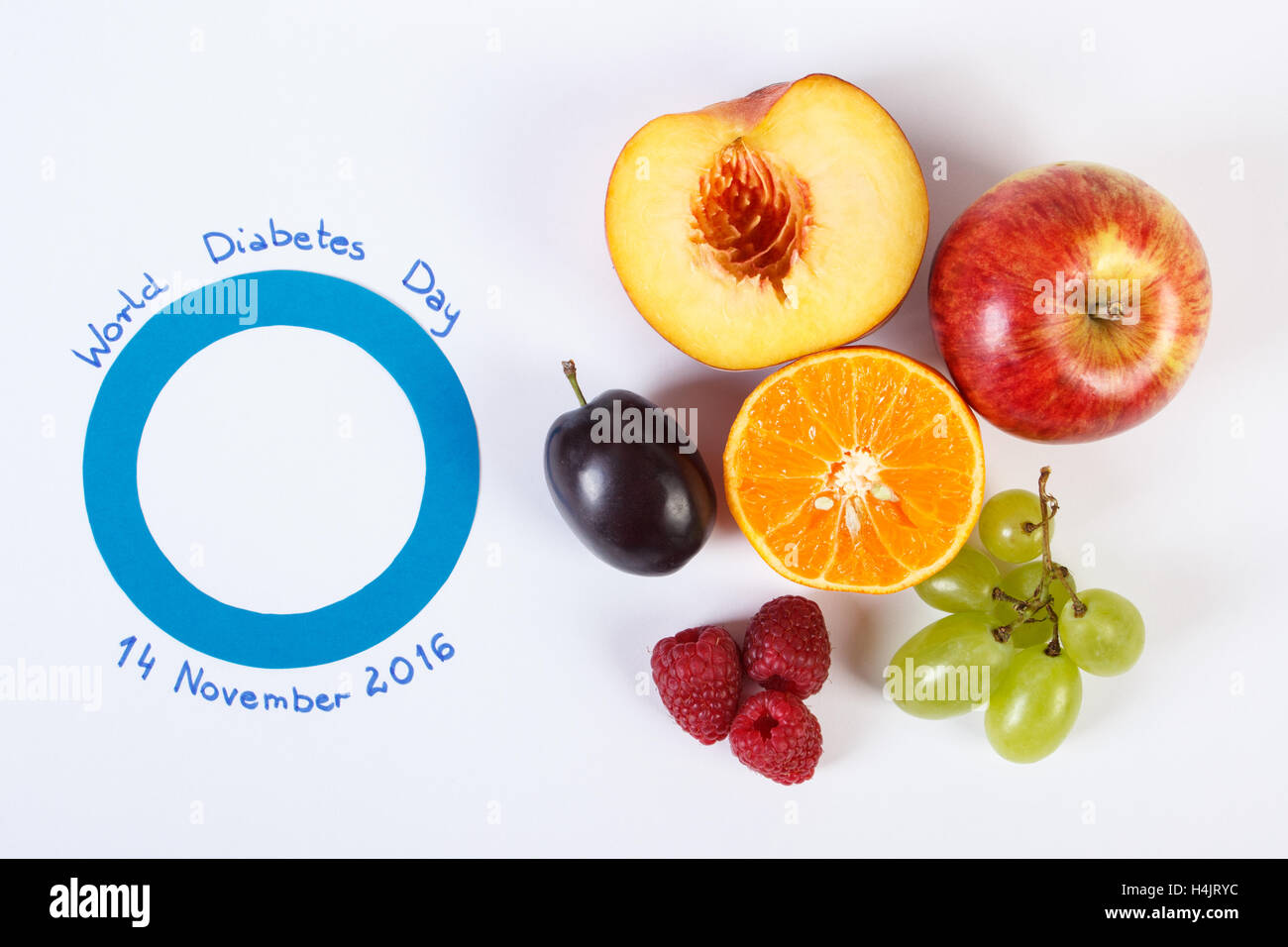 Fresh ripe fruits and blue circle of paper, symbol of world diabetes day and healthy nutrition. White background - Stock Image