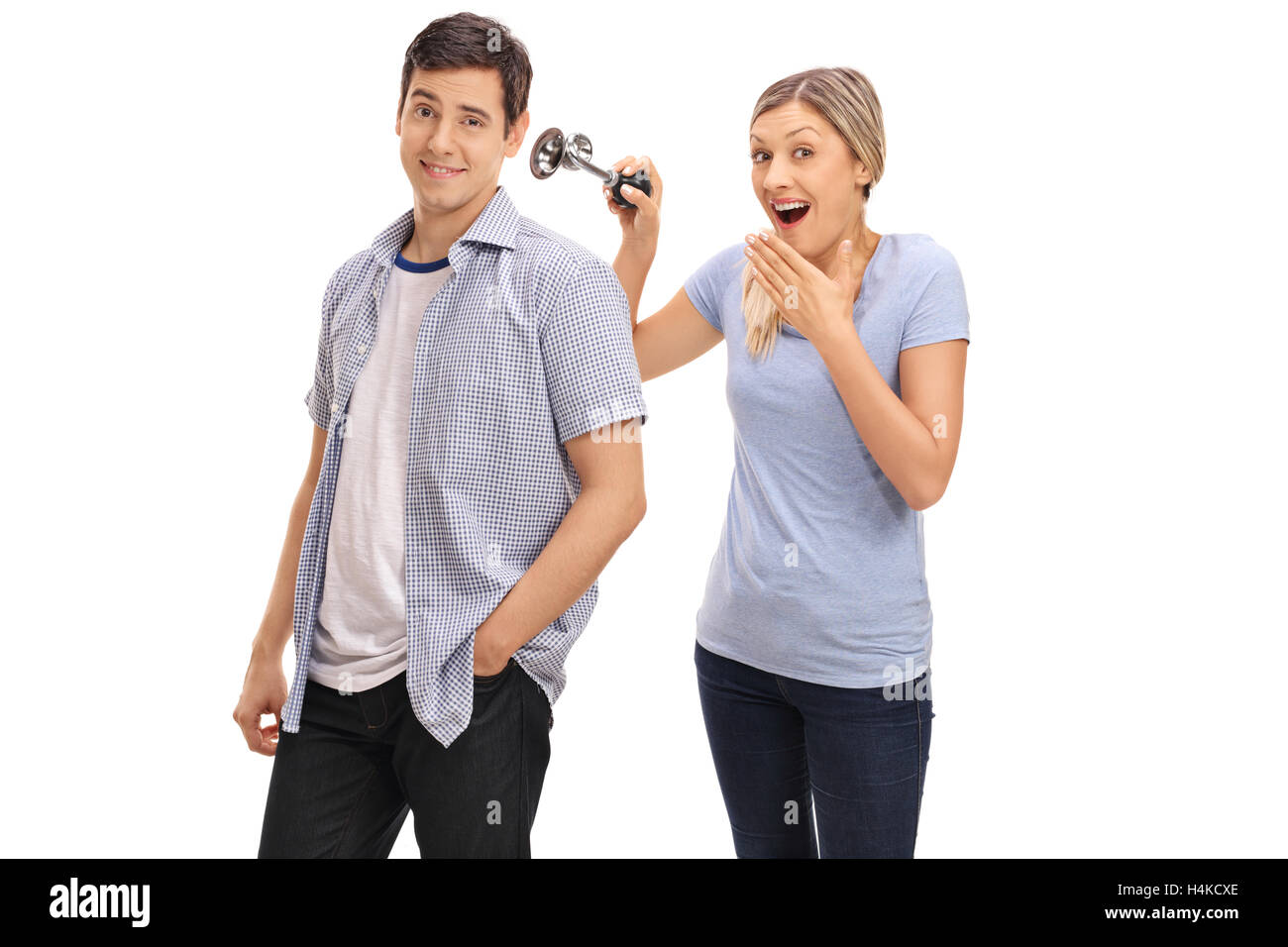 Woman pranking her boyfriend by honking a horn next to his ear isolated on white background - Stock Image