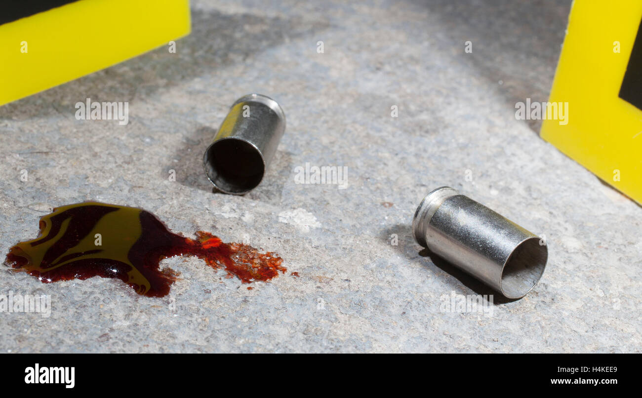 Crime scene with handgun casings, evidence markers and blood on concrete - Stock Image