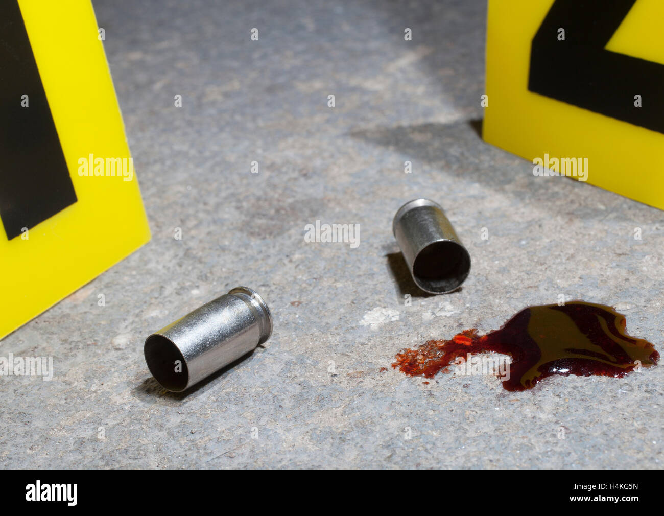 Ammunition and blood on concrete with evidence markers - Stock Image