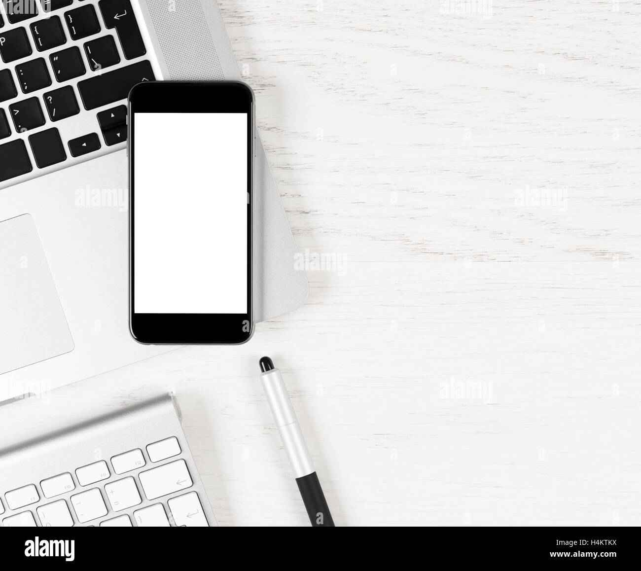 Black smartphone with blank screen lying over silver laptop on white table Stock Photo