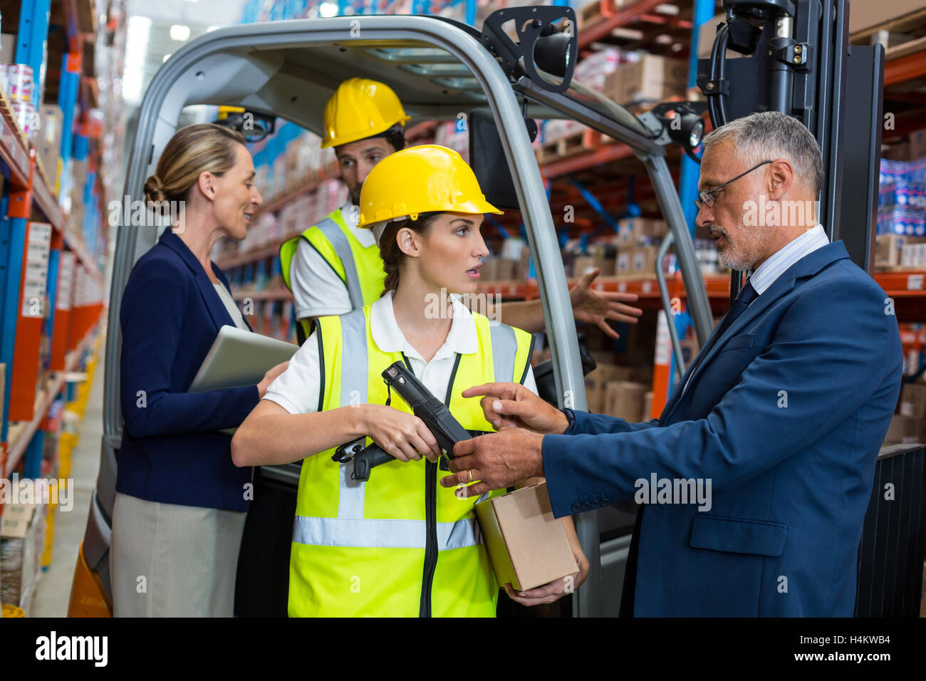 Warehouse manager and client interacting with co-workers - Stock Image