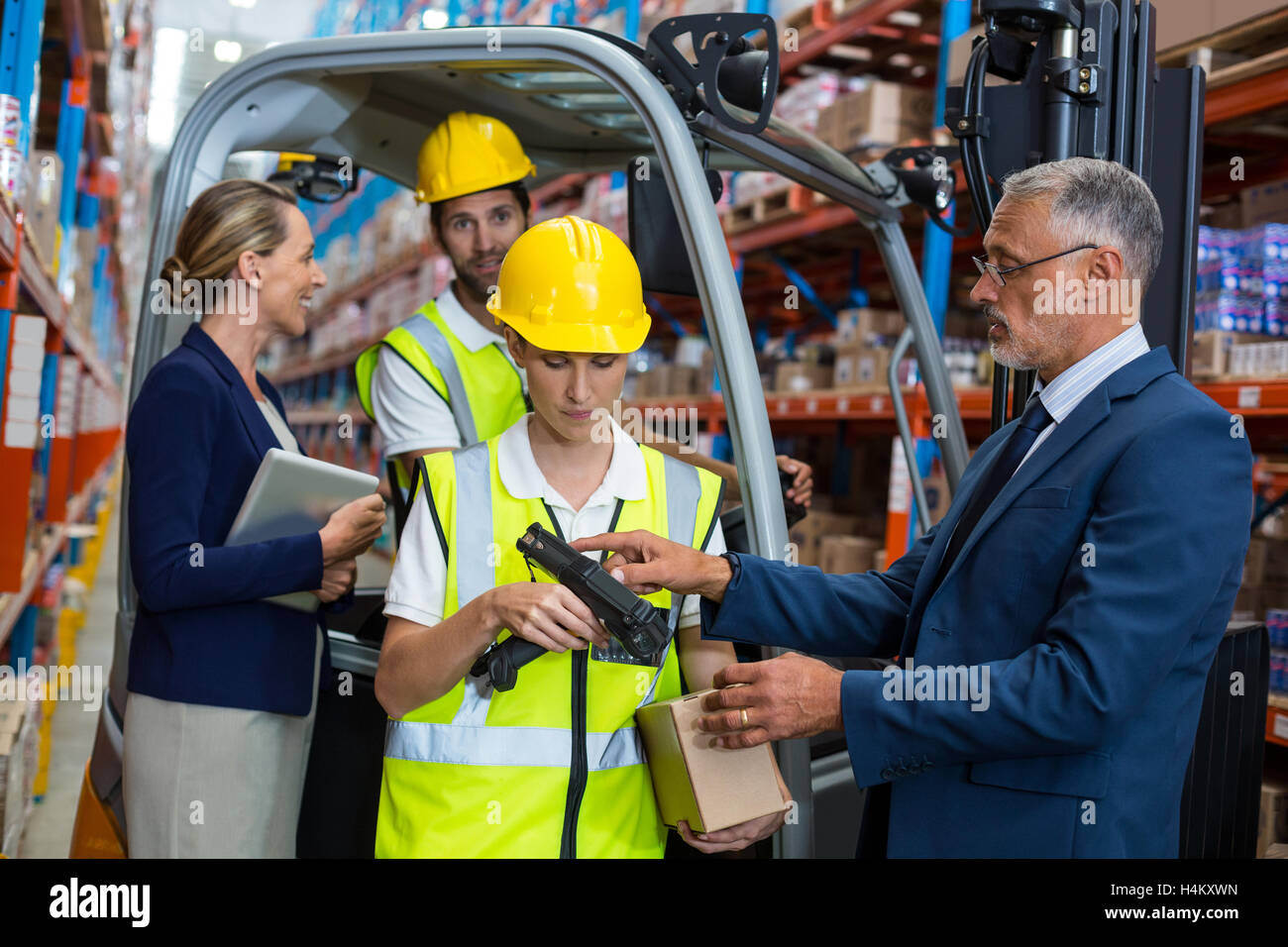 Warehouse manager and client interacting with co-workers Stock Photo