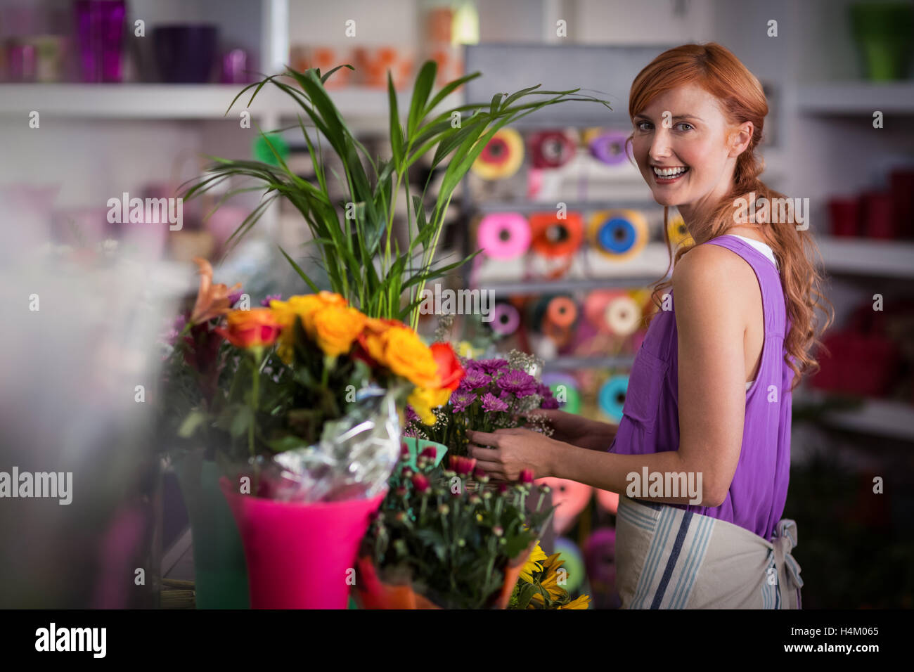 Female florist preparing flower bouquet - Stock Image