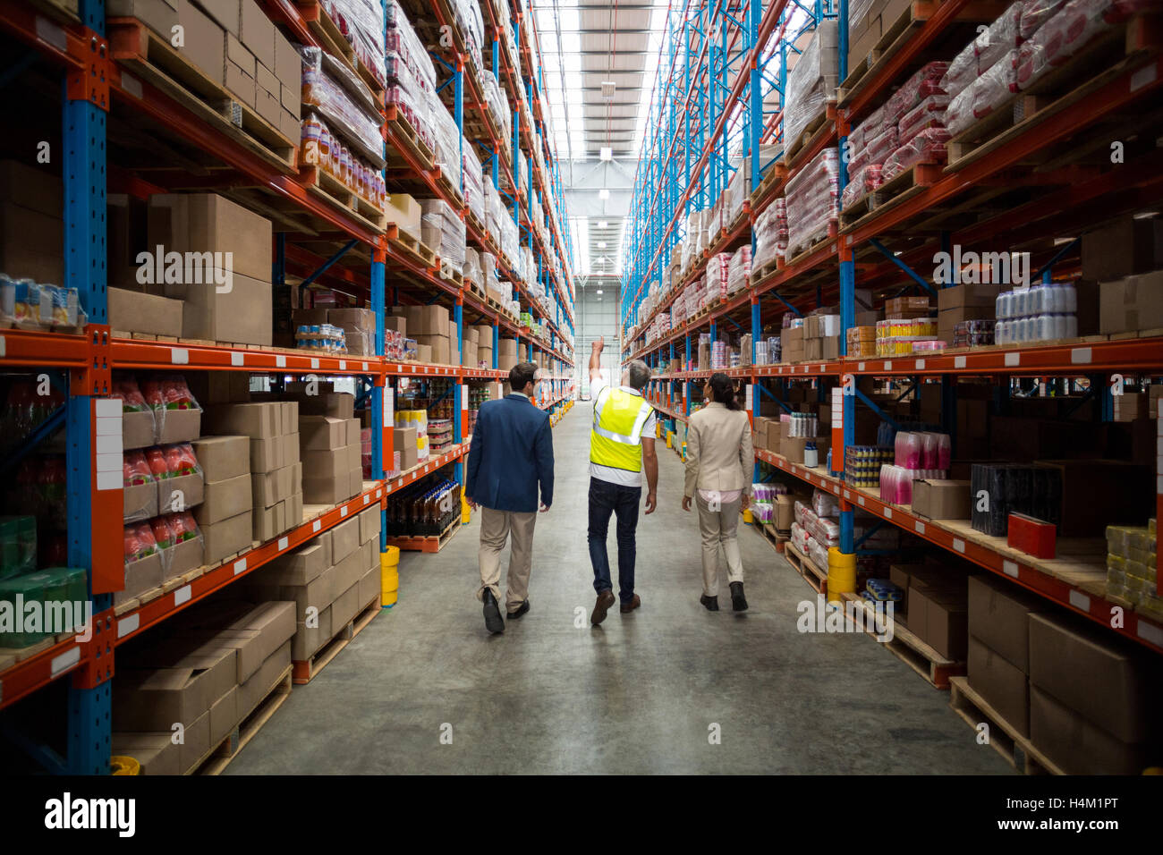 Warehouse team discussing while walking in warehouse - Stock Image