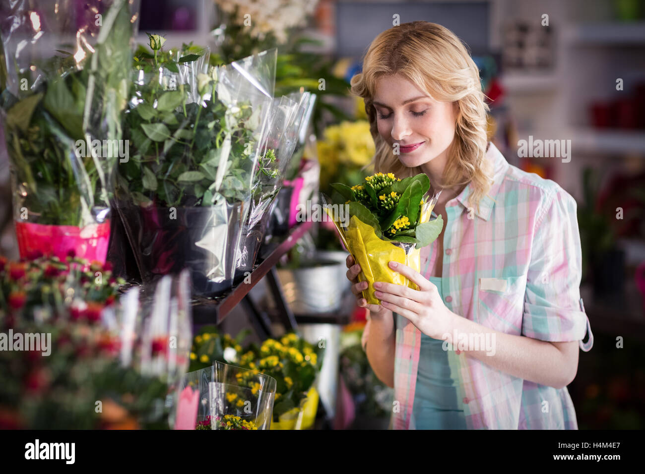 Happy female florist smelling a flower bouquet Stock Photo