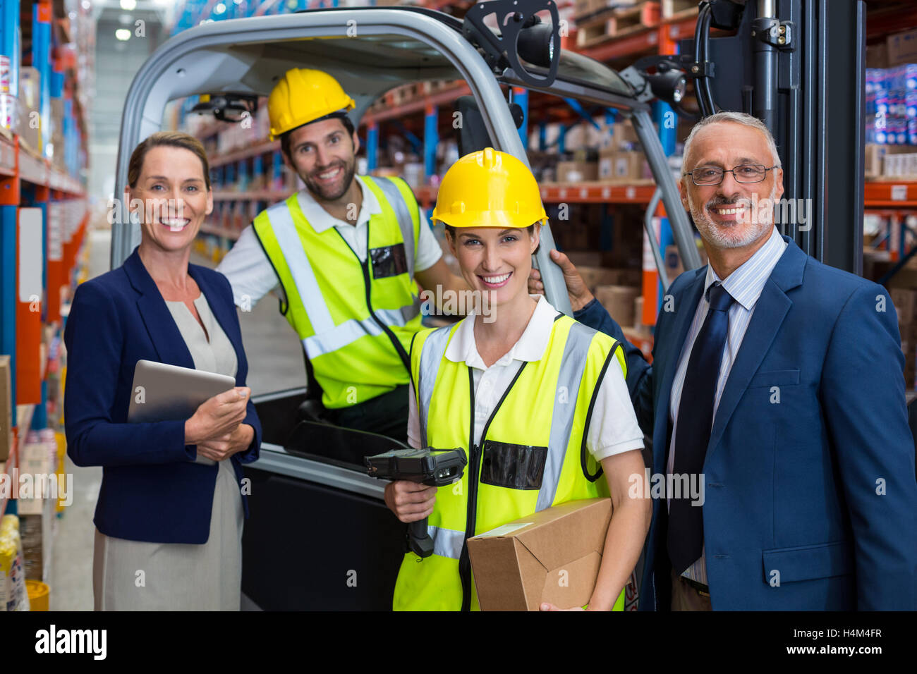 Warehouse manager and client standing with co-workers - Stock Image