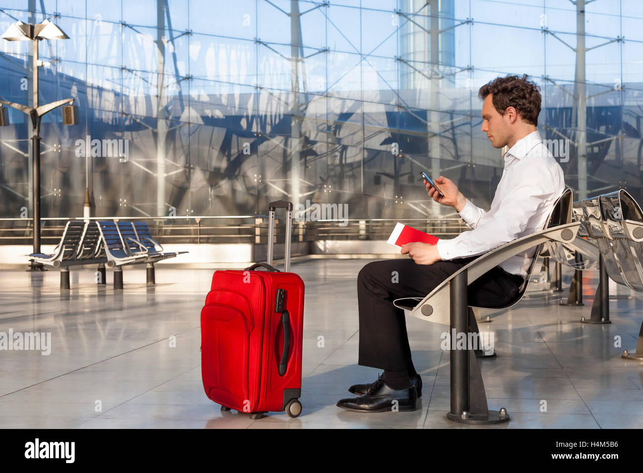 Businessman traveling with smartphone and luggage - Stock Image