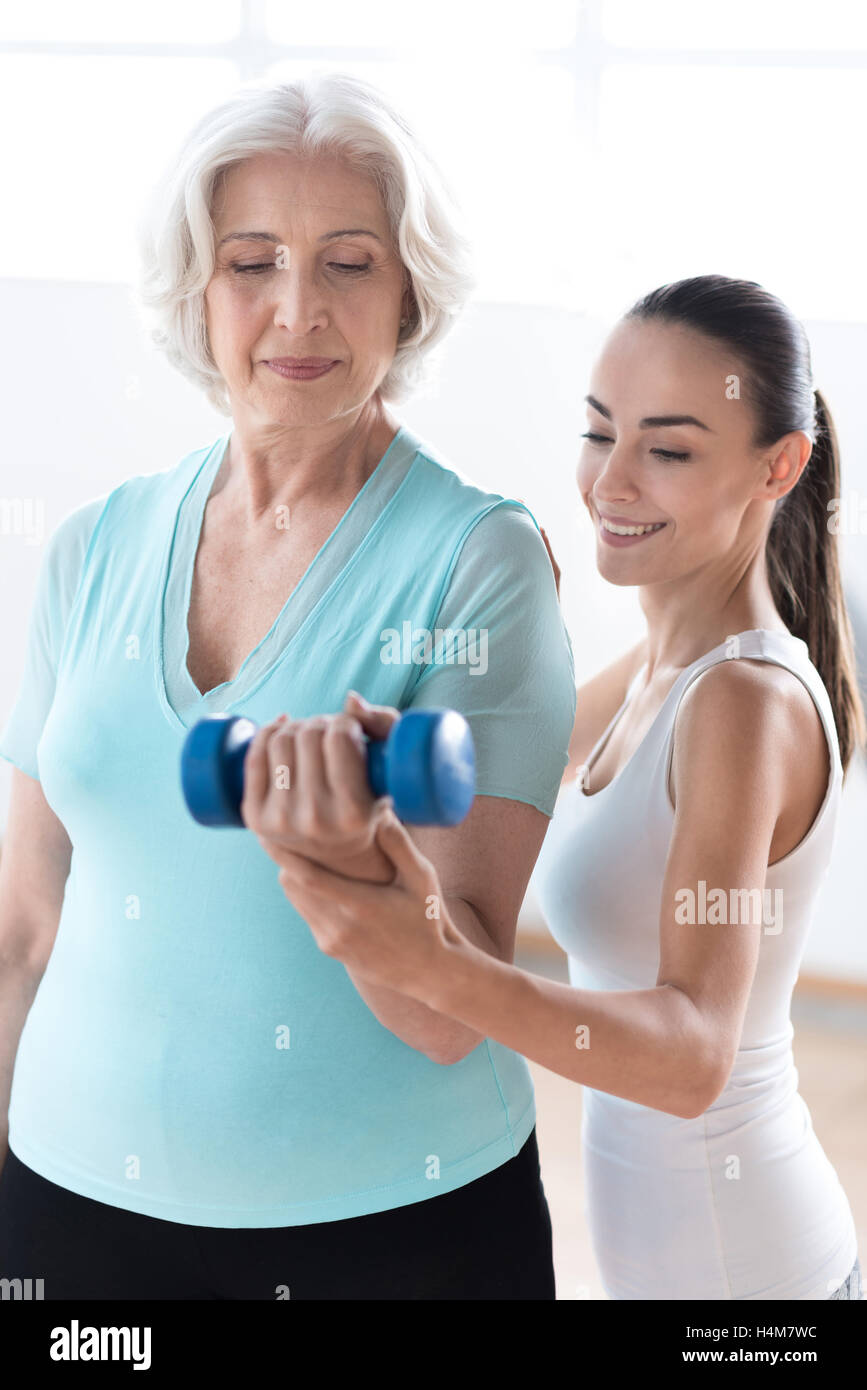 Concentrated serious woman looking at the dumbbell - Stock Image