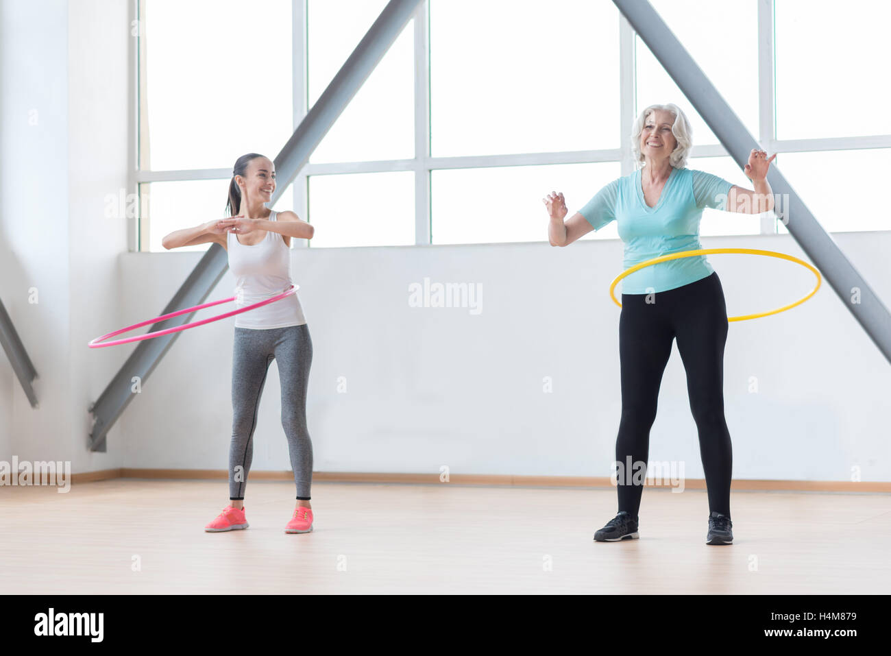 Sporty active women rotating hula hoops - Stock Image