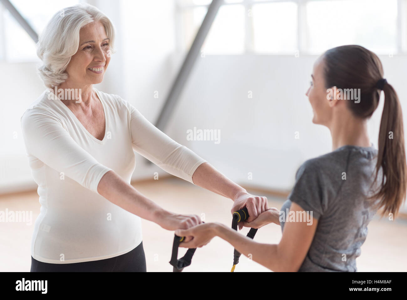 Nice hard working woman using special sports equipment - Stock Image