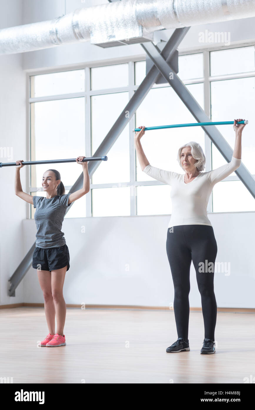 Thoughtful pleasant women holding gymnastic sticks - Stock Image