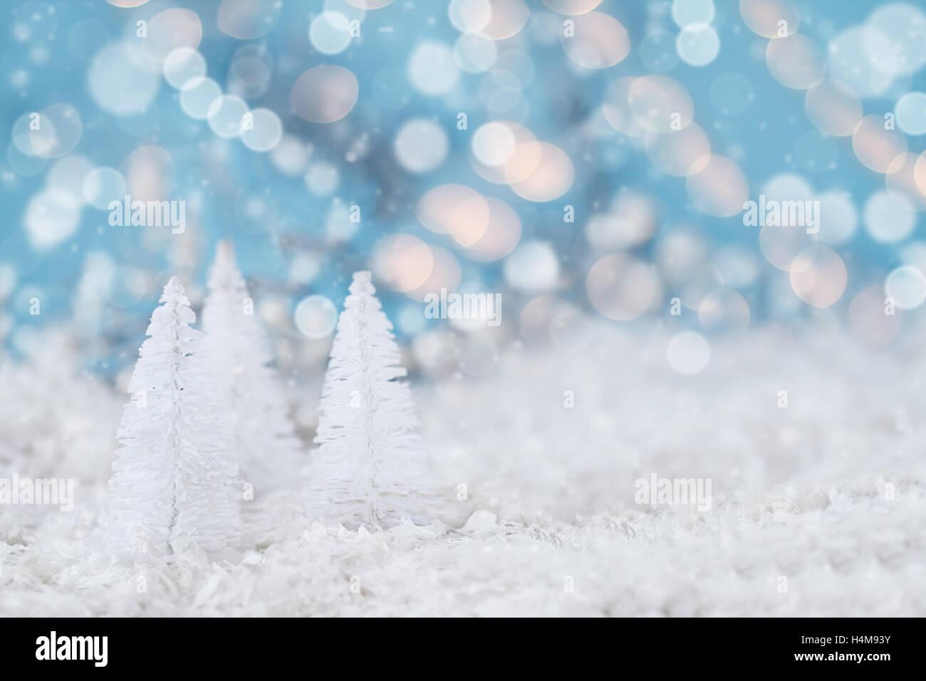White Christmas Background.Miniature White Christmas Trees Against Snowy Bokeh