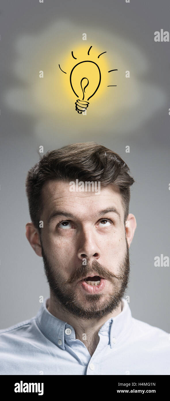 Man is looking reminiscing. Over gray background - Stock Image