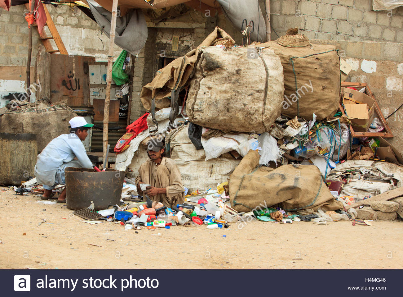 Men sort through trash looking for items of value. - Stock Image