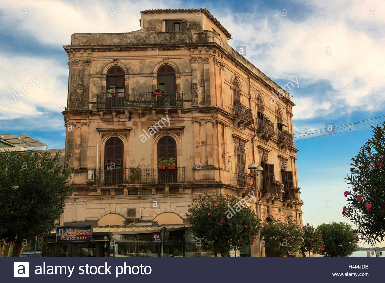 A centuries old, ornate limestone and marble building with arched windows and wrought iron balconies, in Syracuse, Stock Photo
