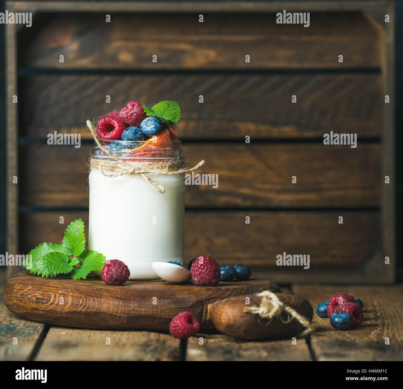 White yogurt in jar with fresh berries, peach, mint leaves - Stock Image
