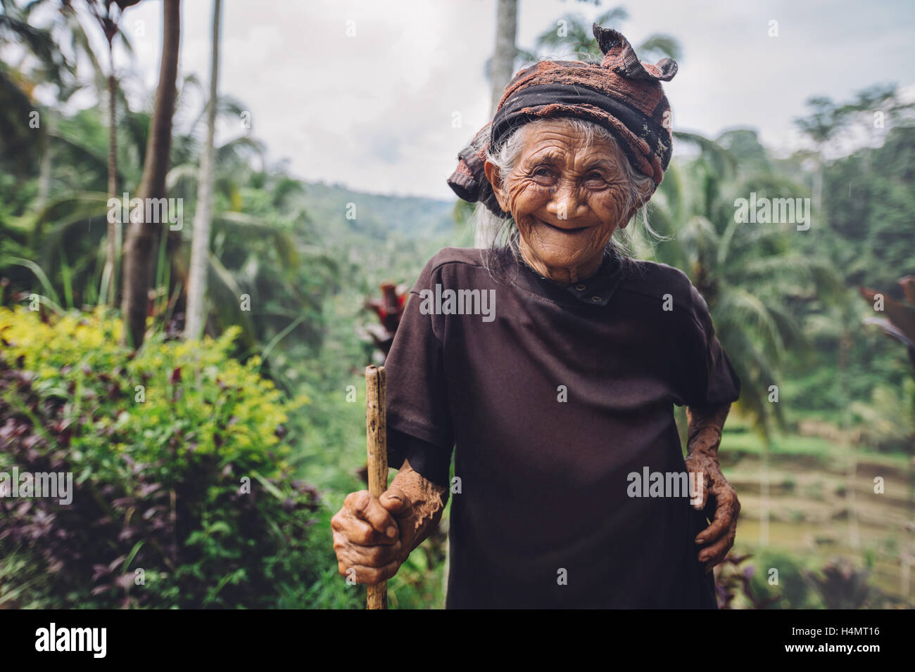 Portrait of senior woman standing with a cane and smiling. Old female with beautiful smile on her face outdoors - Stock Image