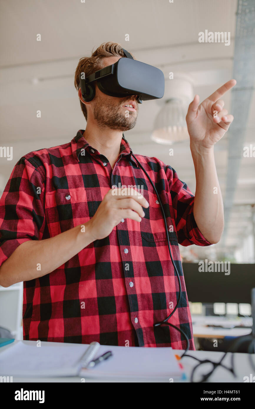 Young man wearing virtual reality glasses and gesturing. Developer using virtual reality simulator headset. - Stock Image