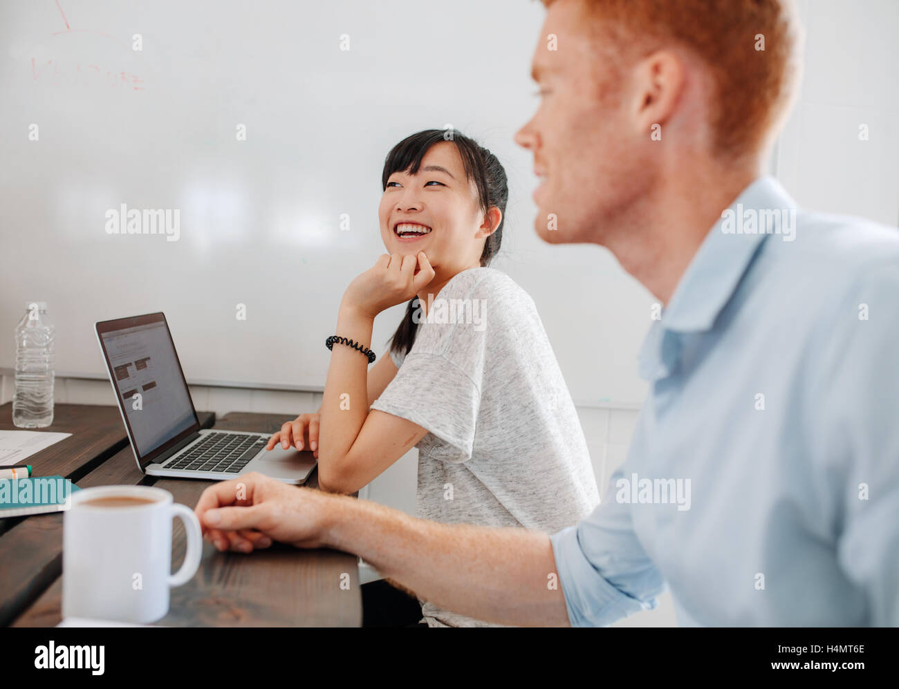 Two happy young business people sitting at conference table during business meeting. Coworkers sitting in boardroom - Stock Image