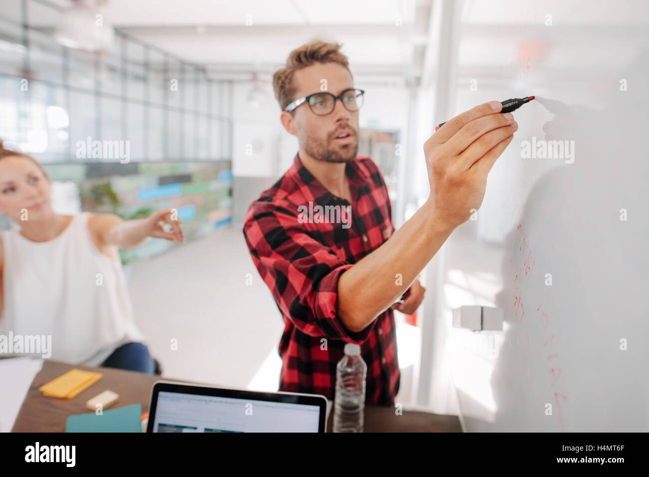 Casual young executive giving a presentation on white board to coworkers. Businesspeople discussing business ideas - Stock Image