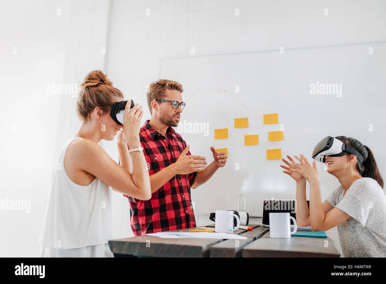 Team of developers working with virtual reality glasses during a business meeting. Young man with female colleagues - Stock Image