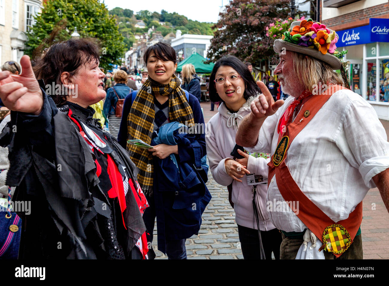 Traditional Morris Dancers In Costume Chat With Japanese Tourists At The Lewes Folk Festival 2016, Lewes, Sussex, Stock Photo