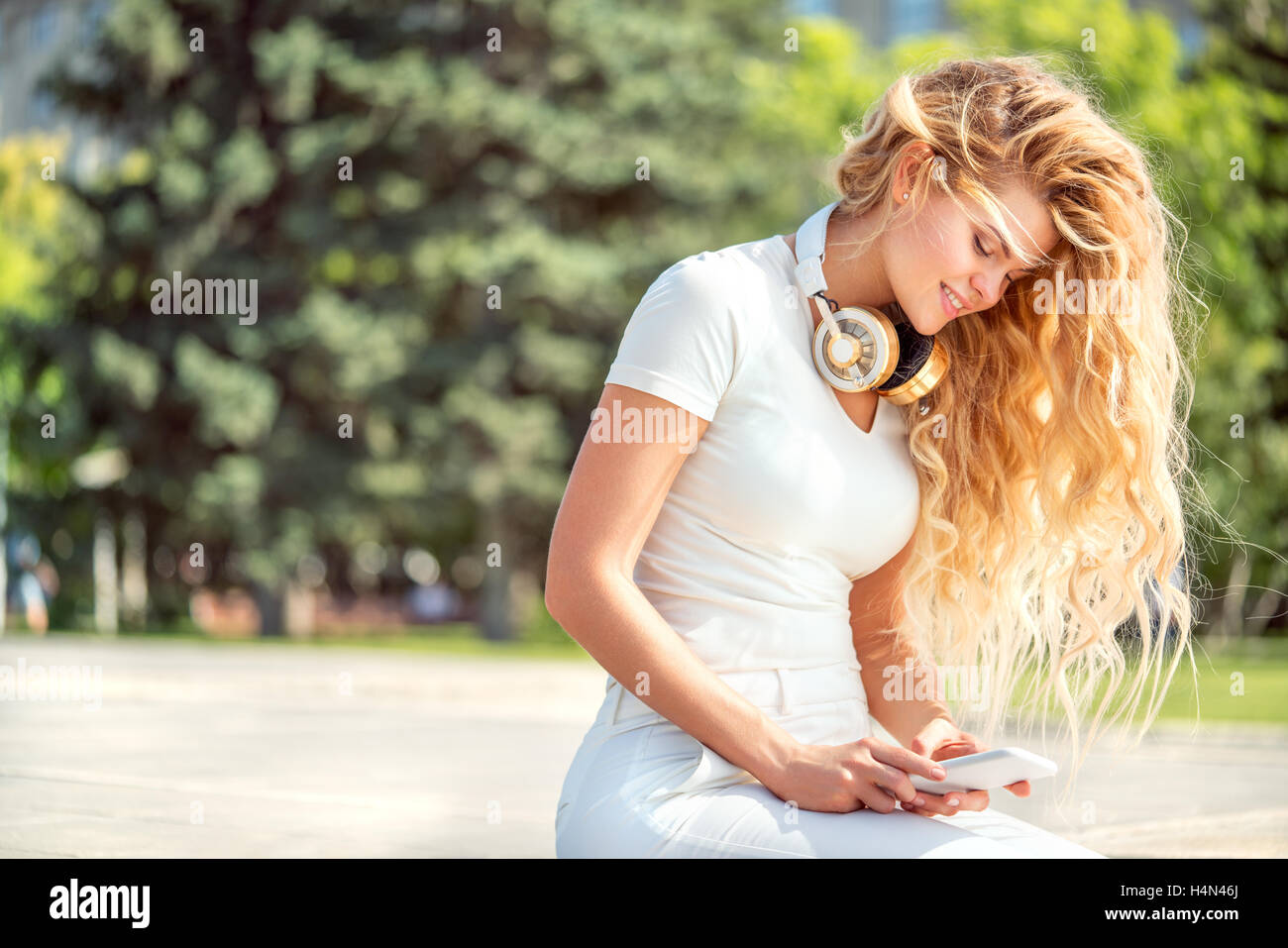 Beautiful young woman with music headphones around her neck, surfing internet on a smartphone and sitting against - Stock Image