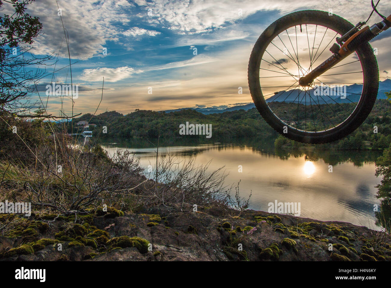 A mountain bike wheel at sunset with the sun reflection in the lake - Stock Image