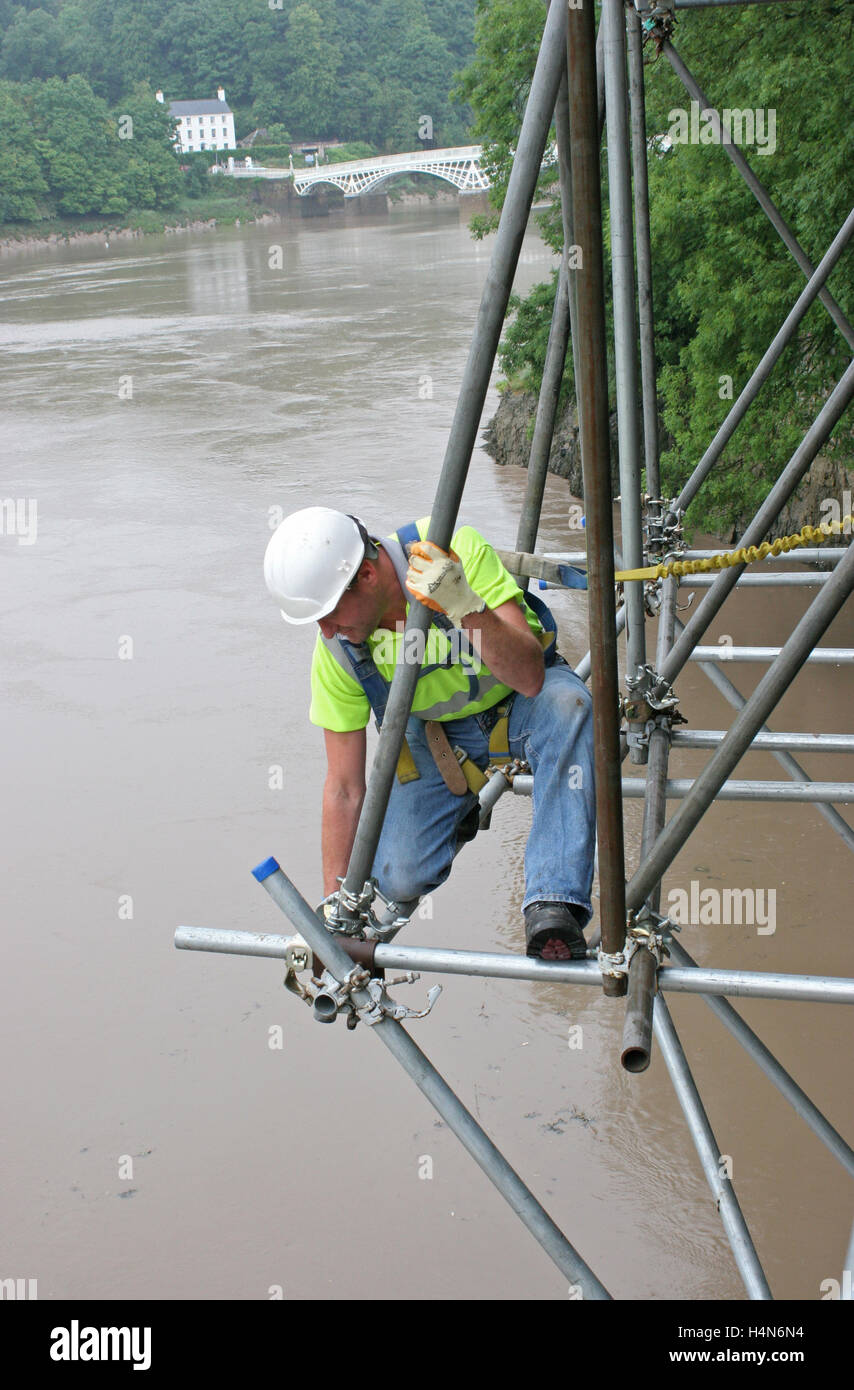 A scaffolder tightens a fitting whilst assembling traditional tube and fittings scaffolding high above a river - Stock Image