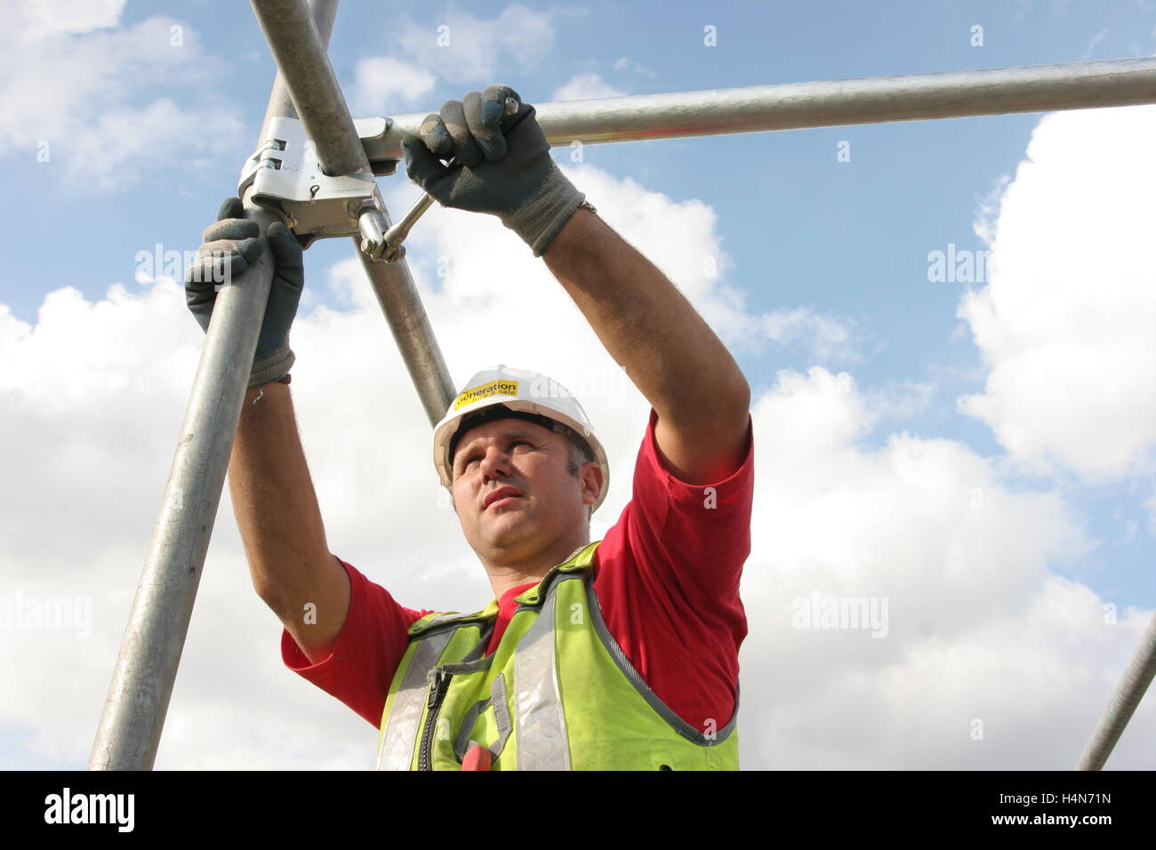 A scaffolder tightens a fitting whilst assembling traditional tube and fittings scaffolding - Stock Image