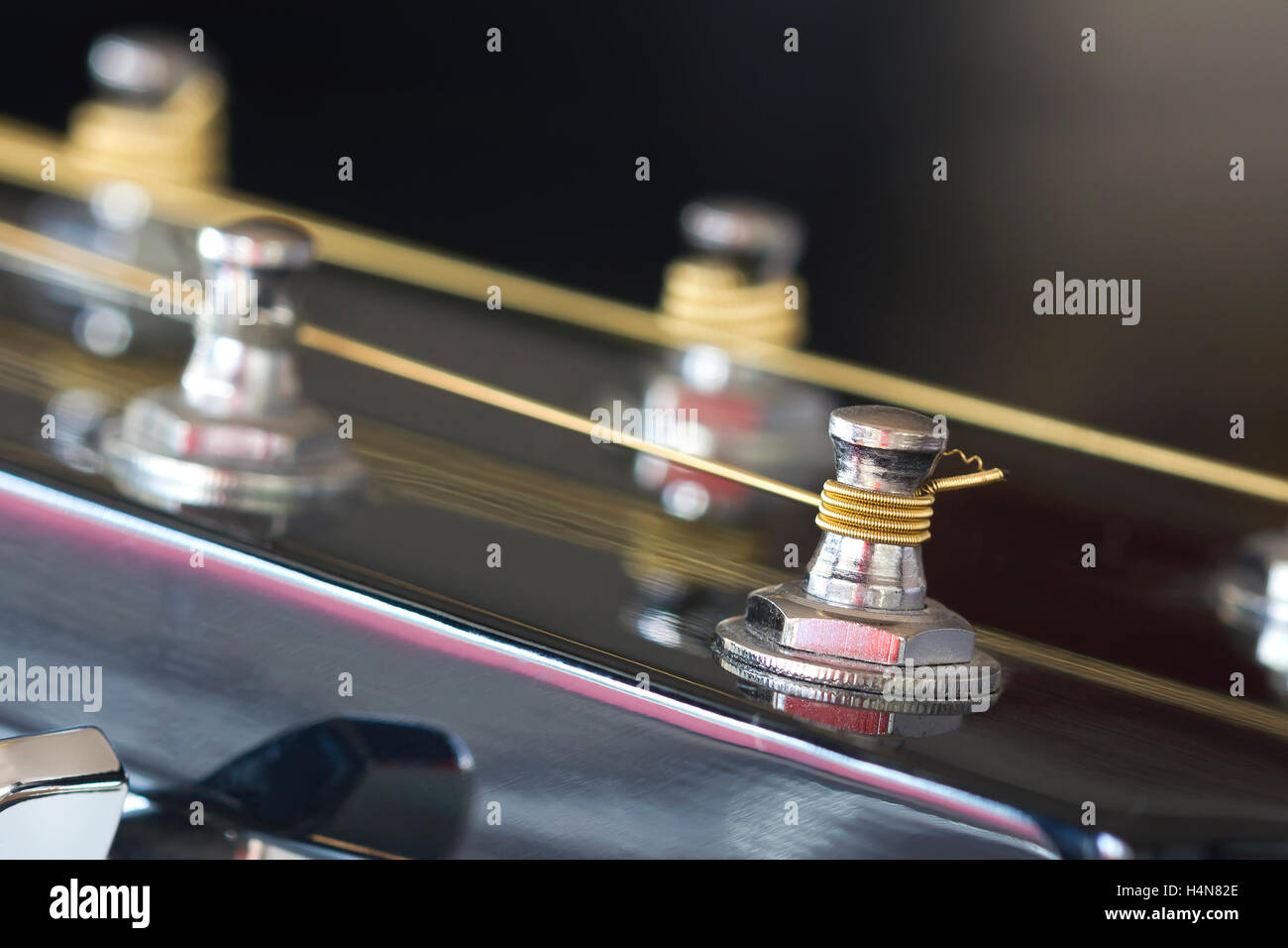 Closeup image of one of a tune post of a guitar. - Stock Image