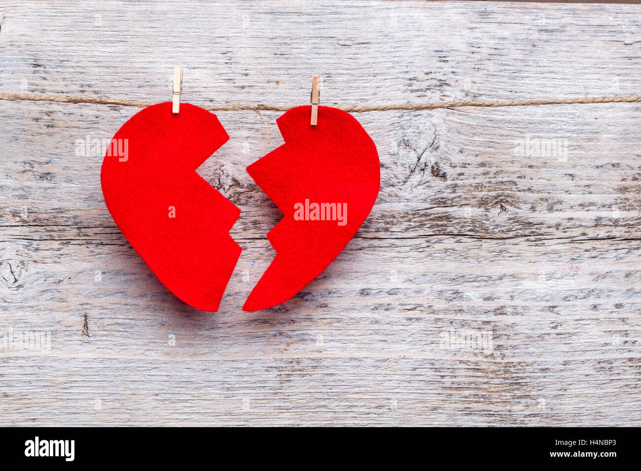 Broken heart hanging on rope - Stock Image