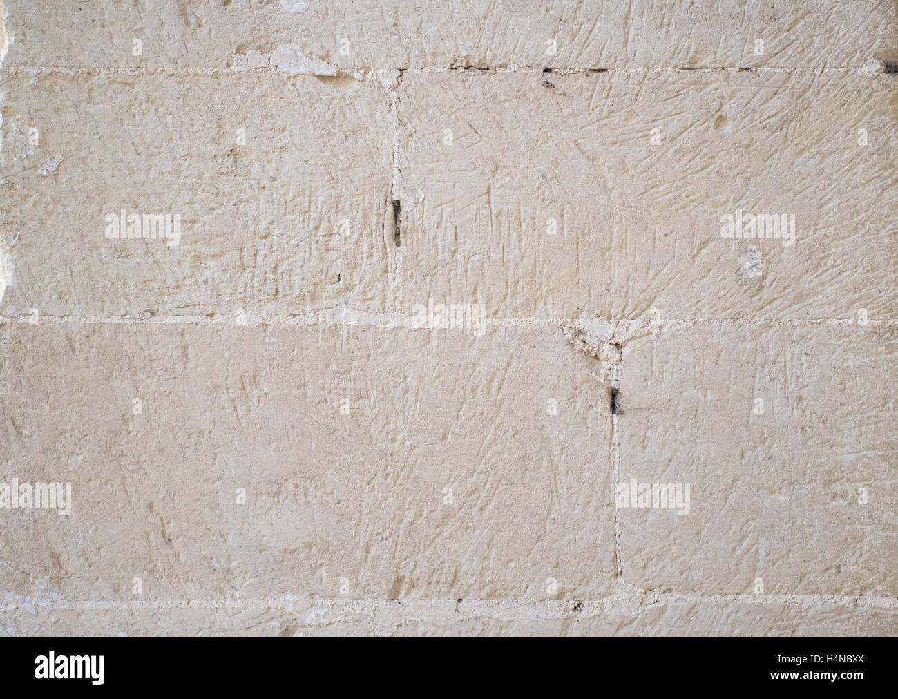 Traditional white stone wall. Detail of a wall made of white limestone bricks. Visible traces of chisel. - Stock Image