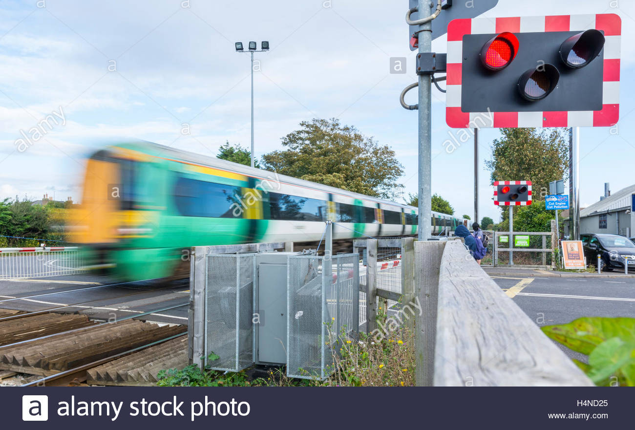 Moving fast. Class 377 Electrostar Southern Rail train showing motion blur moving over a level crossing in Southern - Stock Image